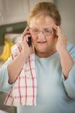 手机的震惊资深妇女在厨房里 免版税图库摄影