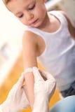 她的投入绷带的实践的医生在一个小男孩的某一创伤 免版税库存照片