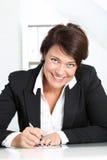 她的服务台的微笑的女实业家 库存照片