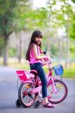 她的桃红色自行车的逗人喜爱的矮小的亚裔女孩 免版税库存照片