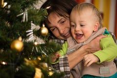 她的母亲的胳膊的逗人喜爱的笑的孩子 免版税库存图片