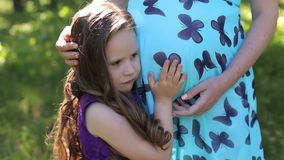她的母亲的腹部的小孩听的婴孩室外在晴朗的自然 股票视频