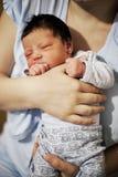 她的母亲胳膊的新出生的女婴 库存图片
