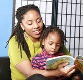 她的母亲读取儿子 免版税库存图片