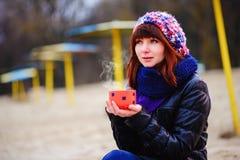 从她的热水瓶的少妇饮用的咖啡,享受秋天晚上由海 库存图片