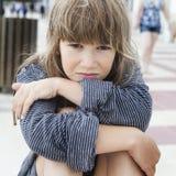 她的父亲不快乐的小女孩佩带的镶边T恤杉  库存图片