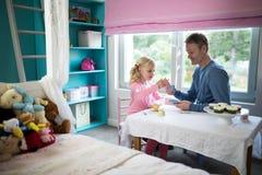 她的父亲的女孩倾吐的茶从玩具厨房集合 库存图片