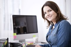 她的看照相机的书桌的愉快的女实业家 免版税库存图片