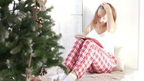 她的睡衣的一名妇女由窗口坐读书的 影视素材