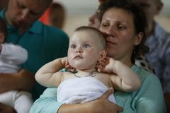 她的胳膊的妈妈施洗的婴孩 库存照片