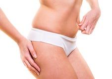 她的腹部有吸引力的女性捏的皮肤  免版税库存图片