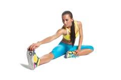 给她的腿加热的女运动员坐在白色的地板 免版税库存照片