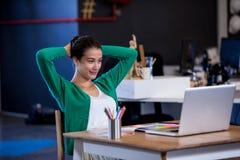 她的膝上型计算机轻松的女实业家前面  库存图片