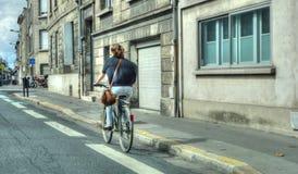 她的自行车的一个女孩在镇里 库存图片