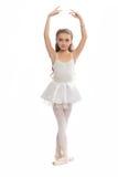 她的舞蹈的女孩给下来接触穿衣她的脚的到达 免版税图库摄影