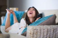 她的说谎在客厅沙发长沙发的20s或30s的年轻美丽和愉快的亚裔中国妇女使用互联网手机laughi 图库摄影
