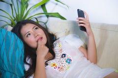 她的说谎在客厅沙发长沙发的20s或30s的年轻美丽和愉快的亚裔中国妇女使用互联网手机lookin 库存照片