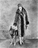 她的长颈鹿的妇女仿造了皮大衣和她的狗(所有人被描述不更长生存,并且庄园不存在 供应商w 免版税库存照片