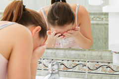 洗她的面孔的少妇 免版税库存图片