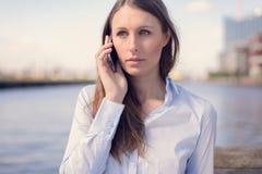她的移动电话联系的妇女年轻人 免版税库存图片