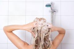 洗她的头发的性感的blondie妇女 免版税库存图片