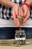 她的婴孩的挽救金钱 图库摄影