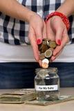她的婴孩的挽救金钱 库存图片