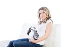 给她的婴孩的美丽的妇女听到音乐 库存照片