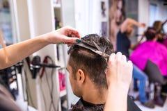 她的年轻客户的无法认出的美发师切口头发 库存图片