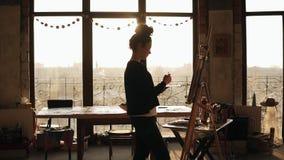 她的20 `的s充分地被集中的老练女性艺术家画在画架的图片 在lits后的太阳上升艺术 影视素材