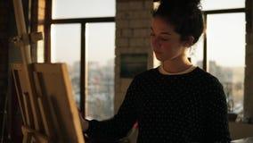 她的20 `的s充分地被集中的老练女性艺术家画在画架的图片 慢动作转动的fotage 影视素材
