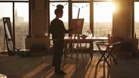 她的20 `的s充分地被集中的老练女性艺术家画在easelin的图片minimalistic顶楼被称呼的艺术 影视素材