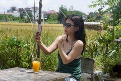 她的20s或30s的微笑亚裔中国的妇女获得乐趣使用手机射击selfie的互联网或聊天饮用的orang 库存图片