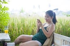 她的20s或30s的微笑愉快的亚裔中国的妇女获得乐趣使用手机的互联网喝橙汁坐的outdoo 图库摄影