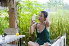 她的20s或30s的微笑愉快的亚裔中国的妇女获得乐趣使用手机的互联网喝橙汁坐的outdoo 库存图片