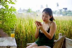 她的20s或30s的微笑愉快的亚裔中国的妇女获得乐趣使用手机的互联网喝橙汁坐的outdoo 免版税图库摄影