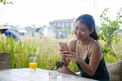 她的20s或30s的微笑愉快的亚裔中国的妇女获得乐趣使用手机的互联网喝橙汁坐的outdoo 免版税库存图片