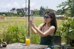 她的20s或30s的愉快的亚裔中国妇女微笑获得乐趣采取与手机的selfie pic对米领域咖啡馆的有orang 免版税库存照片
