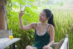 她的20s或30s的愉快的亚裔中国妇女微笑获得乐趣采取与手机的selfie pic对米领域咖啡馆的有orang 库存图片