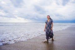 她的20s或30s的穿长的别致的礼服单独走在海滩海的年轻美丽和愉快的亚裔中国妇女画象  图库摄影