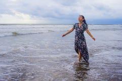 她的20s或30s的穿长的别致的礼服单独走在海滩海的年轻美丽和愉快的亚裔中国妇女画象  免版税库存图片