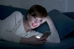 她的20s的使用手机在晚上微笑在互联网的俏丽和愉快的红色头发妇女或30s后说谎在家庭长沙发或床 库存图片