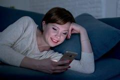 她的20s的使用手机在晚上微笑在互联网的俏丽和愉快的红色头发妇女或30s后说谎在家庭长沙发或床 免版税库存图片