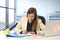 她的30s的妇女在运作在便携式计算机书桌的办公室采取笔记 免版税库存图片