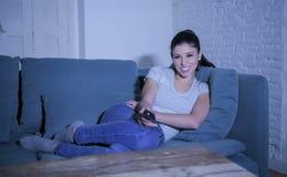 她的30s的年轻美丽和愉快的拉丁妇女拿着电视遥控在家享受客厅长沙发观看的电视节目的 免版税库存图片