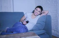 她的30s的年轻美丽和愉快的拉丁妇女拿着电视遥控在家享受客厅长沙发观看的电视节目的 库存图片
