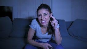 她的30s的年轻美丽和愉快的拉丁妇女拿着电视遥控在家享受客厅长沙发观看的电视节目的 免版税图库摄影