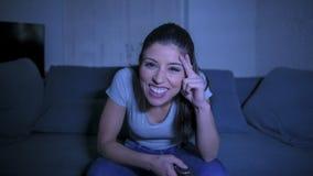 她的30s的年轻美丽和愉快的拉丁妇女拿着电视遥控在家享受客厅长沙发观看的电视节目的 库存照片