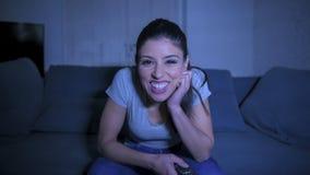 她的30s的年轻美丽和愉快的西班牙妇女拿着电视遥控在家享用客厅长沙发观看的电视的 库存图片