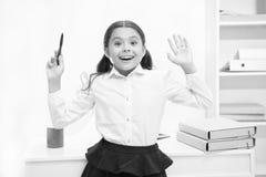 她认识正确答案 儿童女孩佩带校服站立的激动的面孔表示 女小学生聪明的儿童神色 免版税库存图片